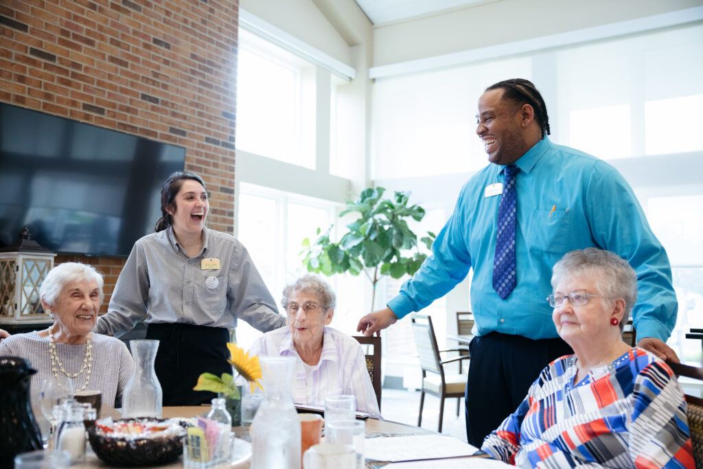 Morrison Living servers smiling with residents in community at the table
