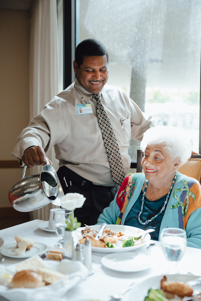 Server pouring water for resident at table