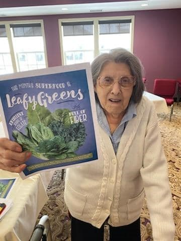 resident with leafy greens sign